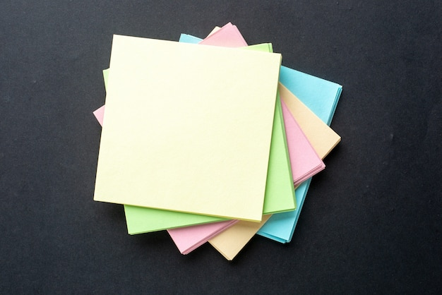 Close up view of stacked sticky coloured note cubes on isolated black wave background with free space