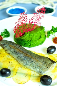 Close up view of steamed fish with broccoli pureed and sliced potatoes and black olives on white plate on blue