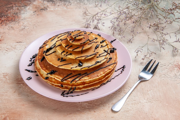 Close up view of stuffy pancakes decorated with chocolate syrup on a white