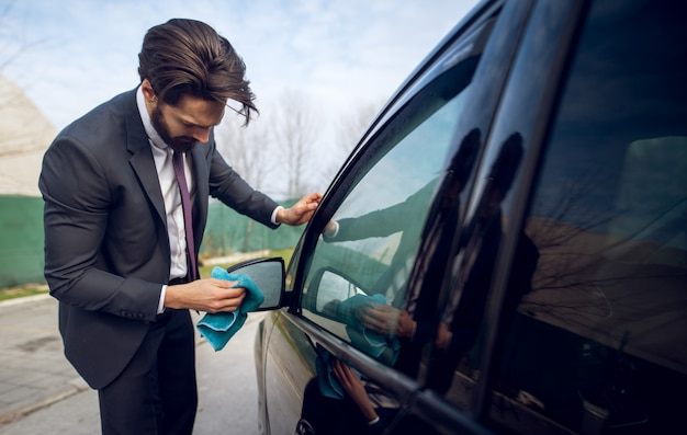 Close up view of stylish focused hardworking young businessman cleaning rearview mirror of his black car with a blue microfiber cloth.