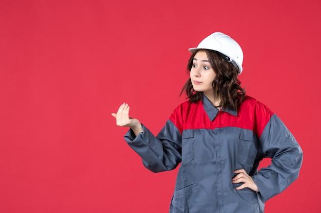 Vista ravvicinata del costruttore femminile sorpreso in uniforme con elmetto e chiamare qualcuno sulla parete rossa isolata