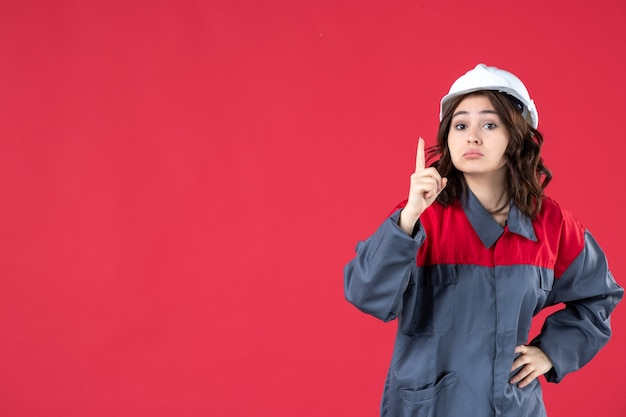 Close up view of surprised female builder in uniform with hard hat and pointing up on isolated red wall