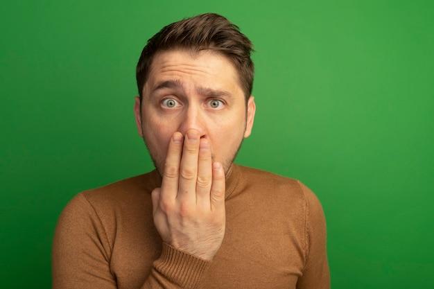 Vista ravvicinata di un bel giovane biondo sorpreso che tiene la mano sulla bocca guardando la parte anteriore isolata sulla parete verde con spazio di copia