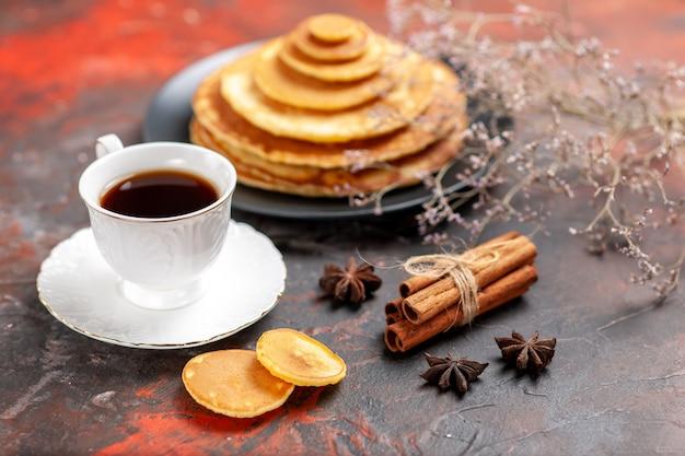 Vista ravvicinata della gustosa colazione con frittelle morbide e una tazza di tè accanto al lime alla cannella