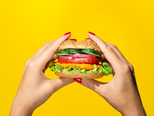 Close up view tasty burger on yellow background