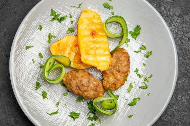Vista ravvicinata di una gustosa cena con patate pasto cotoletta su un piatto bianco sul tavolo scuro