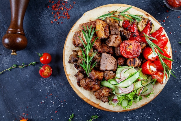 Close up view on tasty grilled meat with vegetables on georgian pita. shashlik or barbecue meat on pita. shish kebab, traditional georgian cuisine food. copy space. top view. dark background