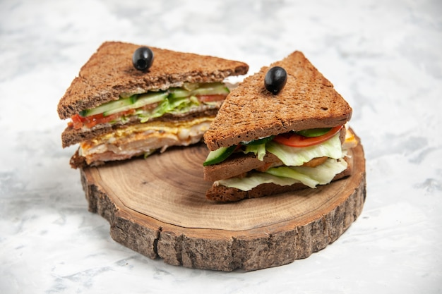 Close up view of tasty sandwich with black bread decorated with olive on a wooden cutting board on stained white surface with free space