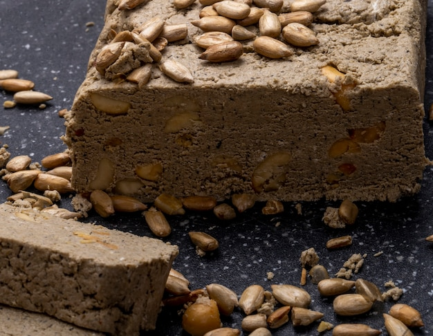 Close up view of tasty slices of halva with sunflower seeds on a black board