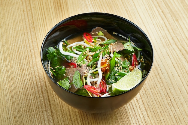Close up view on tasty, traditional pho vietnamese soup consisting of broth, rice noodles, herbs, and meat