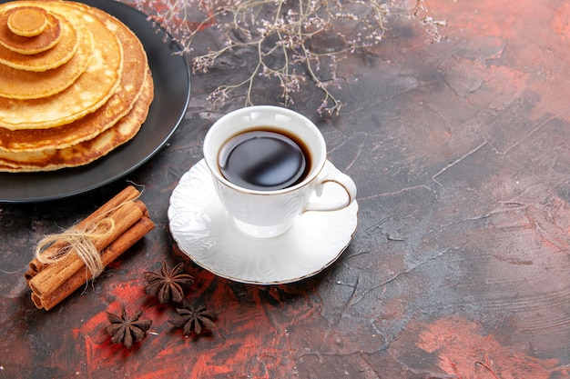 Close up view of tea in a white cup with pluffy pancakes