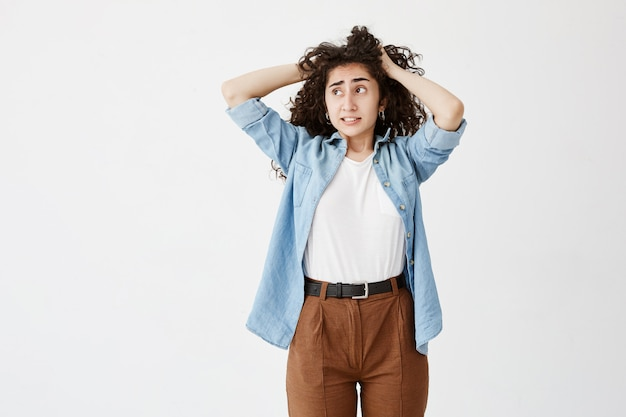 Close up view of teenage girl in denim shirt and brown trousers, looking aside with puzzled face expression, clenches teeth, touching her long dark wavy hair. face expression and emotions concept
