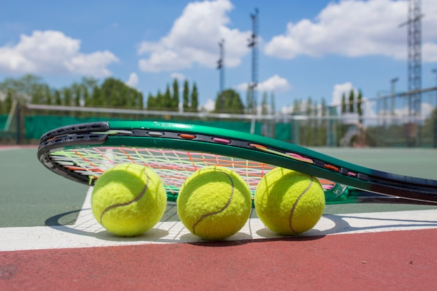 Close up view of tennis racket and balls on the tennis court