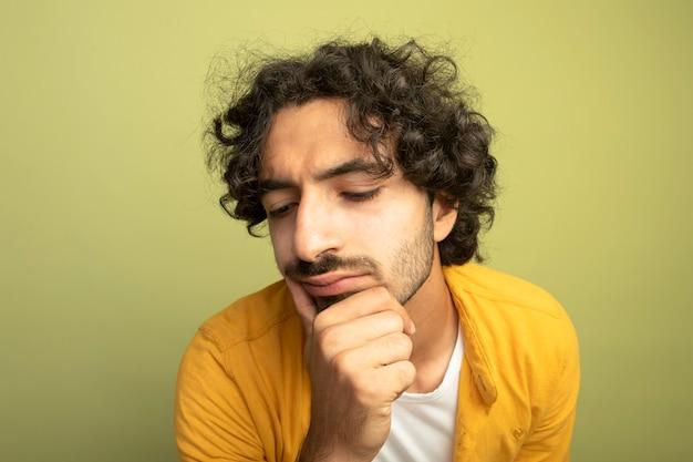 Vista ravvicinata del giovane uomo bello premuroso che tocca il mento guardando verso il basso isolato sulla parete verde oliva