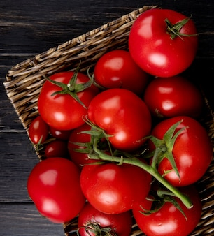 Close-up view of tomatoes in basket plate on wooden table