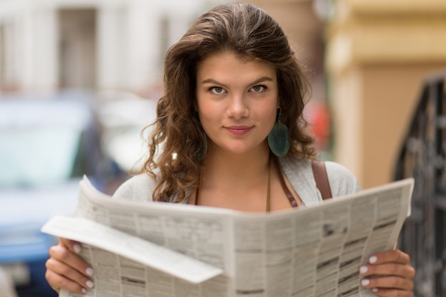 Close up view of tourist girl holding newspaper in her hands.