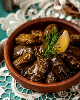 Close up view of traditional dolma in grape leaves in a clay bowl