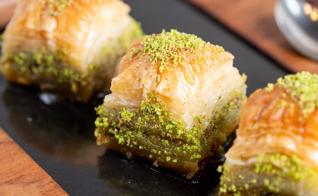 Close up view of traditional turkish baklava with pistachio on a black board