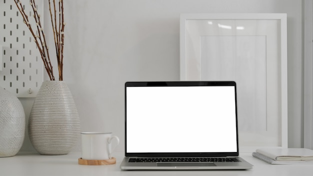 Close up view of trendy with blank screen laptop,  frame and decorations