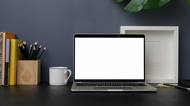 Close up view of trendy workplace with laptop on black table with grey wall