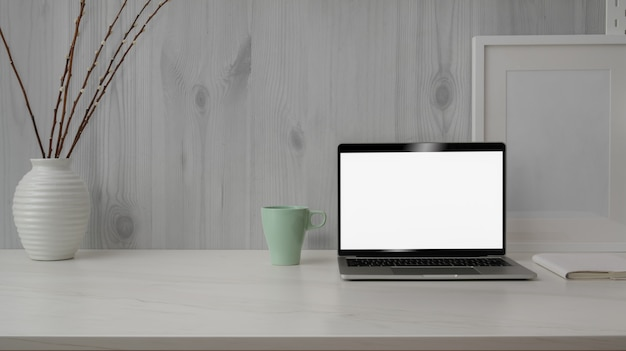 Close up view of trendy workspace with blank screen laptop on marble desk with white modern rustic wall