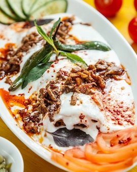 Close up view of turkish iskender kebab served with sour yogurt on white plate