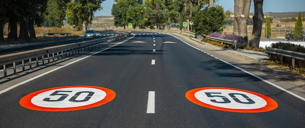 Close-up view of two 50 km per hour, speed limit signs painted on asphalting road. panoramic banner view.