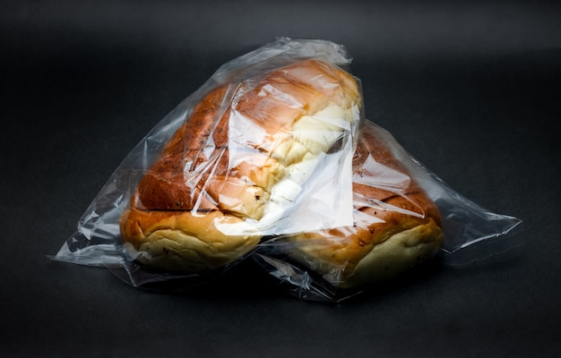 Close up view of two delicious wheat bread inside of transparent polybag on dark texture background