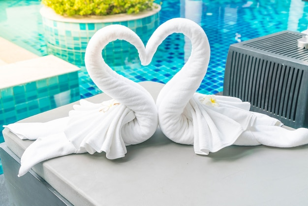 Close up view of two nice towels swans on bed
