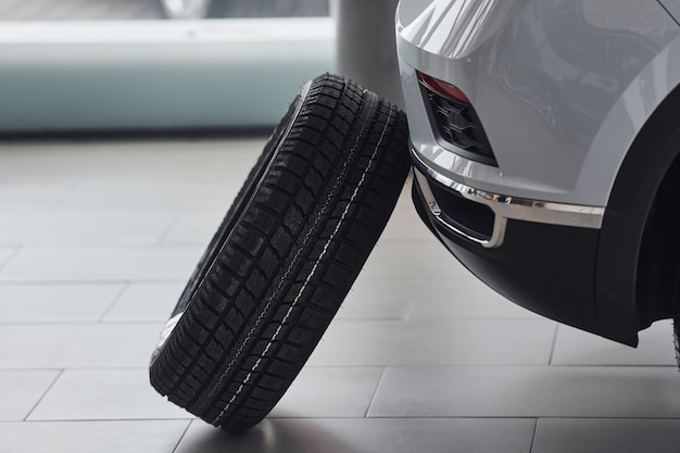 Close up view of tyre that leaning on front of the white car indoors