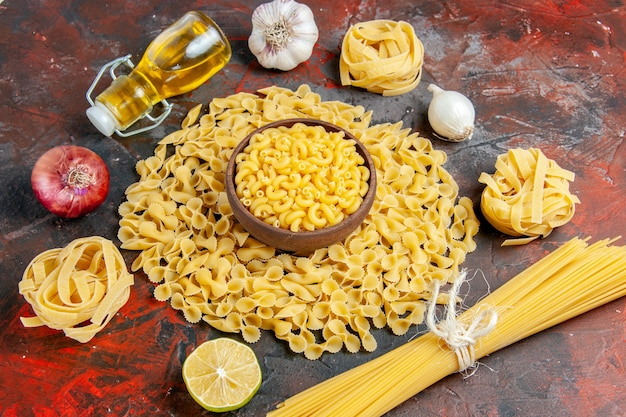 Close up view of uncooked pastas in various forms as spaggeti garlic and onion oil bottle on mixed color table