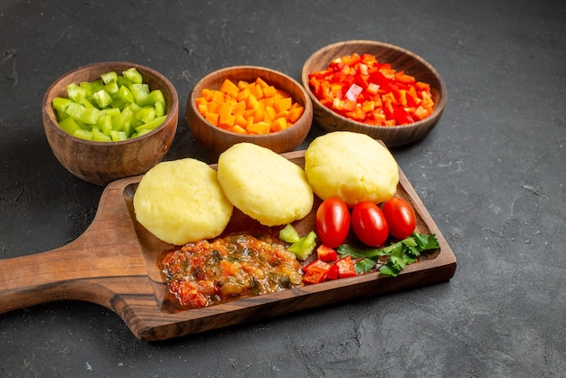 Close up view of uncooked vegetables on a cutting board and chopped foods on the black