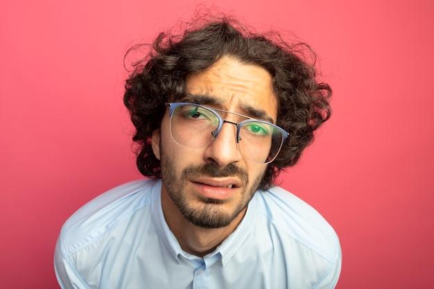 Vista ravvicinata del giovane uomo caucasico bello dispiaciuto con gli occhiali isolati sulla parete cremisi