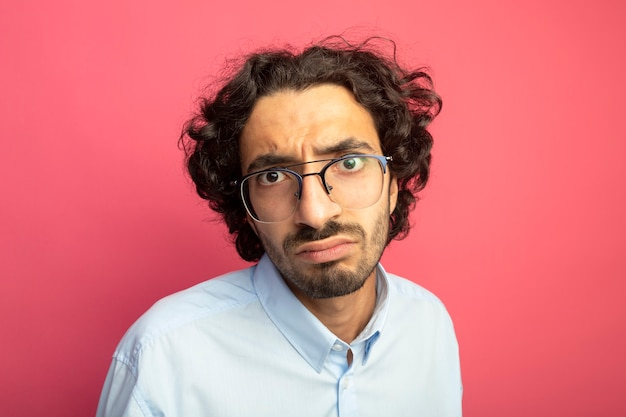 Vista ravvicinata del giovane uomo bello dispiaciuto con gli occhiali guardando la parte anteriore isolata sul muro rosa