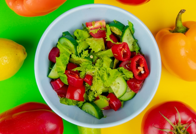 Close-up view of vegetable salad in bowl with pepper tomato lemon on green and yellow background