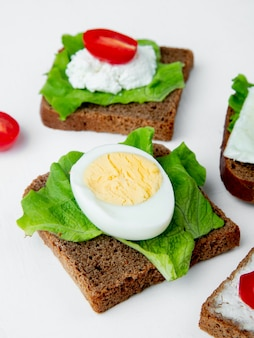 Close-up view of vegetables as boiled egg and spinach on loaf of bread on white background