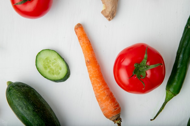 Close-up view of vegetables as carrot cucumber tomato and pepper on white background