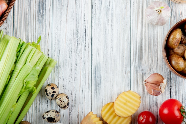 Close up view of vegetables as celery egg potato garlic tomato on wooden background with copy space