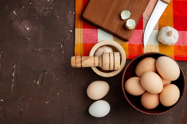 Close-up view of vegetables as egg and garlic with knife on maroon background with copy space
