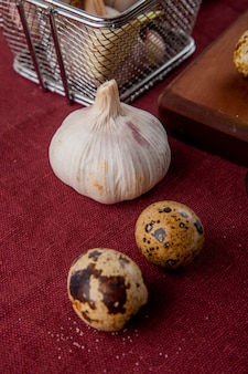 Close-up view of vegetables as garlic and egg on burgundy background
