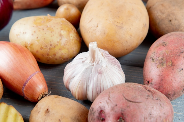 Close up view of vegetables as garlic onion and potato on wooden background