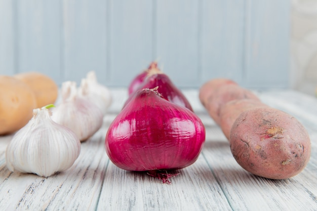 Close up view of vegetables as garlic onion and potato on wooden surface and background with copy space