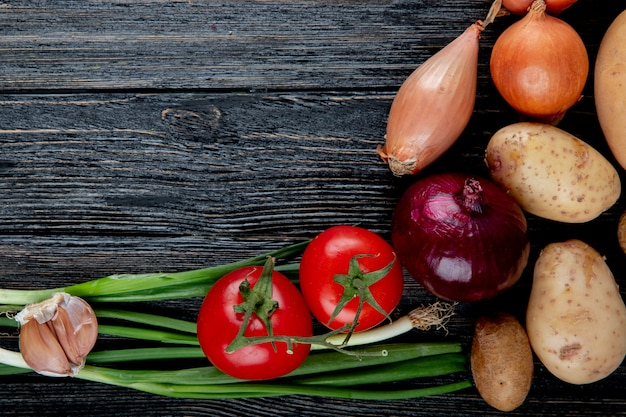Close up view of vegetables as garlic scallion tomato potato and onion on wooden background with copy space