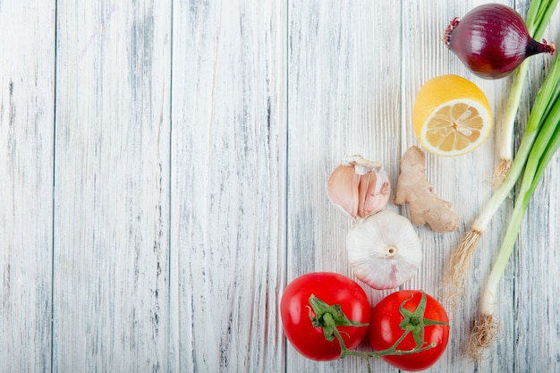 Close up view of vegetables as onion scallion ginger garlic tomato with lemon on wooden background with copy space