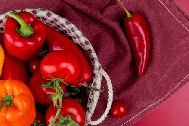 Close-up view of vegetables as pepper tomato cucumber in basket on bordo cloth