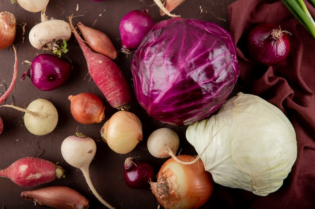 Close-up view of vegetables as purple and white cabbages radish onion on maroon background