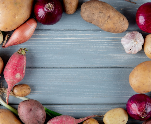 Close up view of vegetables as radish onion potato garlic set in circular shape on wooden background with copy space