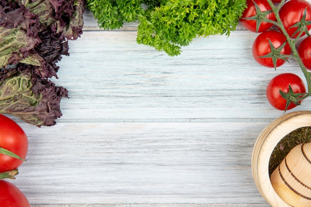 Close-up view of vegetables as tomato basil coriander with garlic crusher on wooden table with copy space