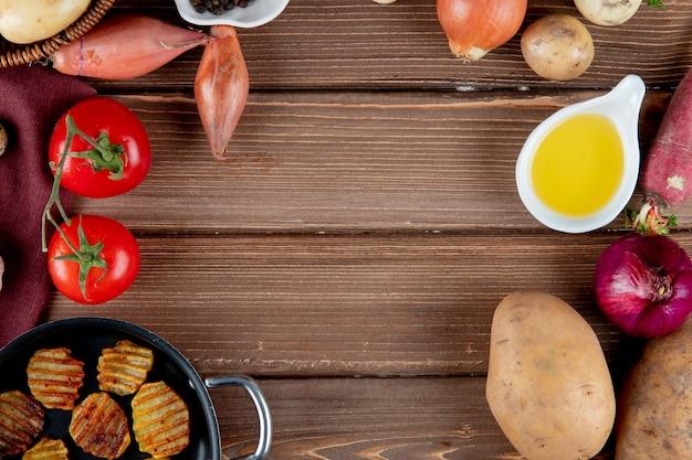Chiuda sulla vista delle verdure come patata della cipolla del pomodoro con burro e patatine fritte su fondo di legno con lo spazio della copia