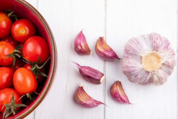 Close up view of vegetables as tomatoes in bowl and garlic bulb and cloves on wooden wall
